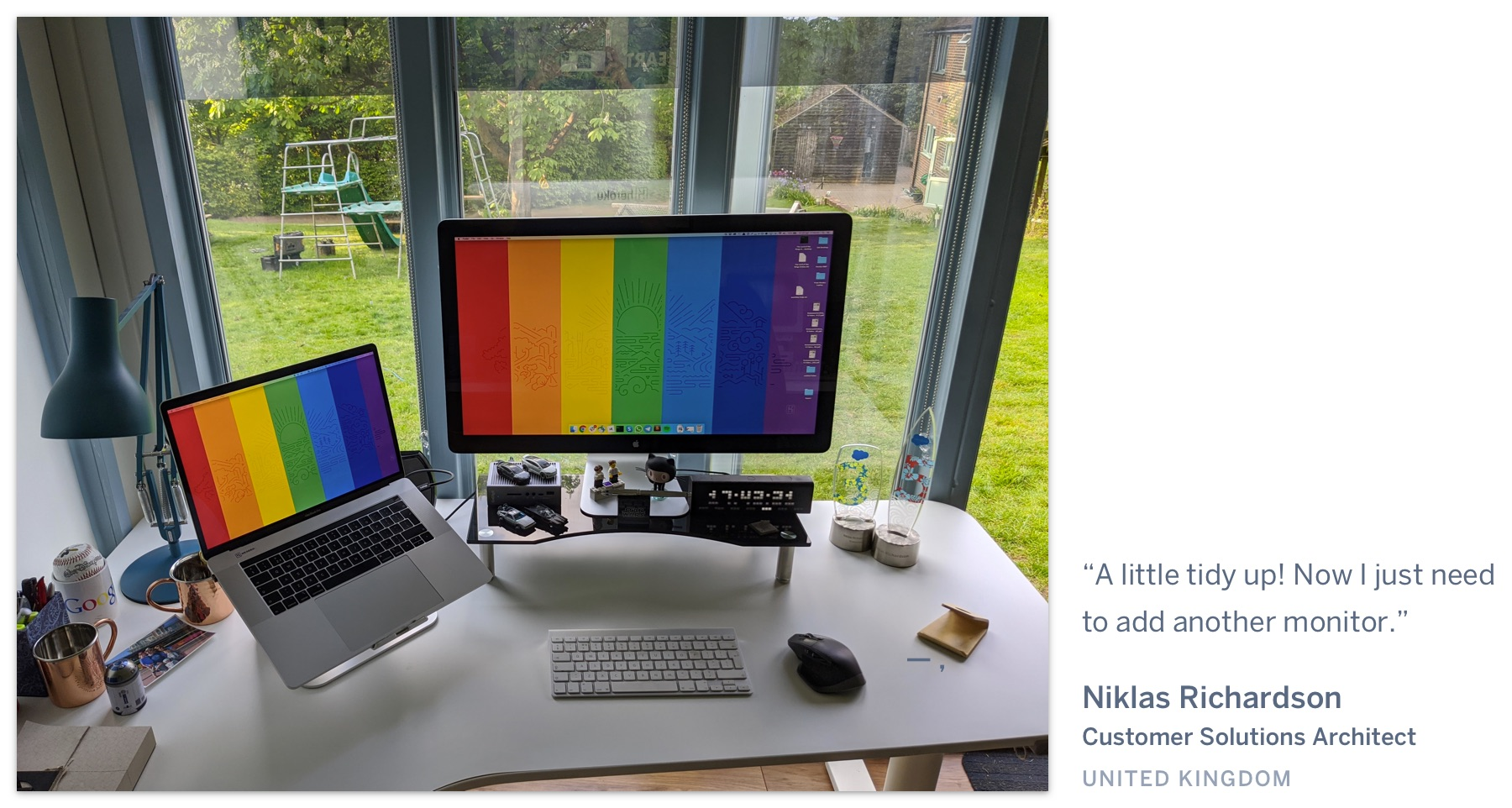 "A computer on a desk with a pride wallpaper, in a shed with a view of a grassy backyard. ""A little tidy up! Now I just need to add another monitor."" Niklas Richardson, Customer Solutions Architect, United Kingdom."